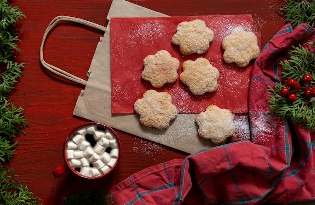 Koekjes op rode houten tafel met rode kop koffie en boodschappentas, leveringsconcept.