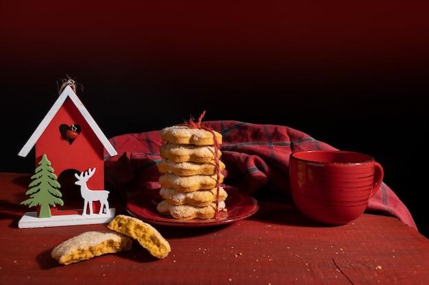 Koekjes op rode houten tafel met rode kop koffie en nieuwjaarsspeelgoed instellen
