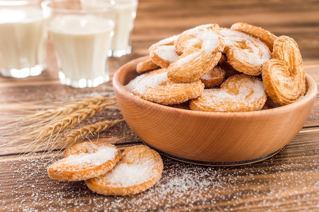 Koekjes op tafel bestrooid met suiker en melk in een glas