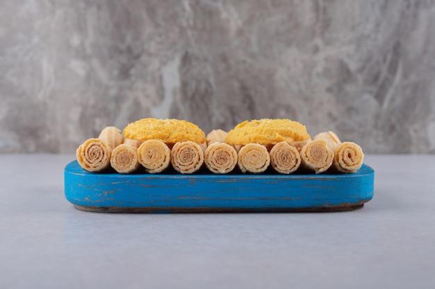 Koekjes op wafelbroodjes op het houten dienblad, het marmer.