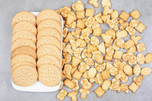 Koekjes opgesteld op een plaat naast verspreide koekjesschips op marmeren achtergrond. hoge kwaliteit foto