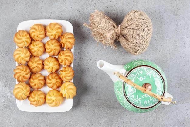 Koekjes opgesteld op een schaal naast een zak en een theepot op marmeren oppervlak
