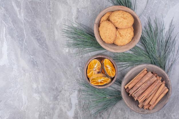 Koekjes, pijpjes kaneel en stukjes sinaasappel in houten kopjes