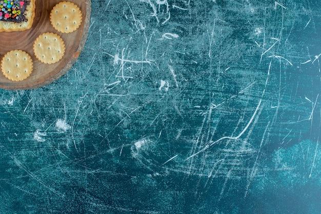 Koekjes rond een hartvormige cake op een bord op blauwe achtergrond. hoge kwaliteit foto