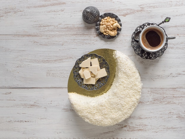 Koekjescake bestrooid met witte chocolade in de vorm van een halve maan, geserveerd met dadels en een koffiekopje