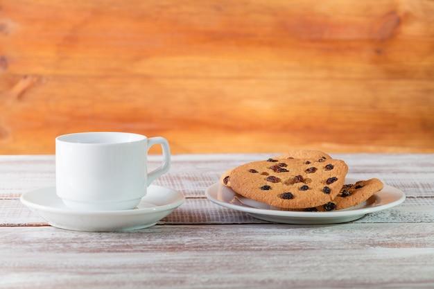 Koekjeschocolade en thee op een houten lijst