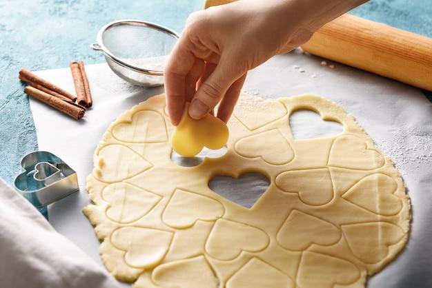Koekjesdeegharten ter beschikking op blauwe achtergrond met deegroller, zeef en kaneel. proces van het koken van koekjes voor de valentijnsdag