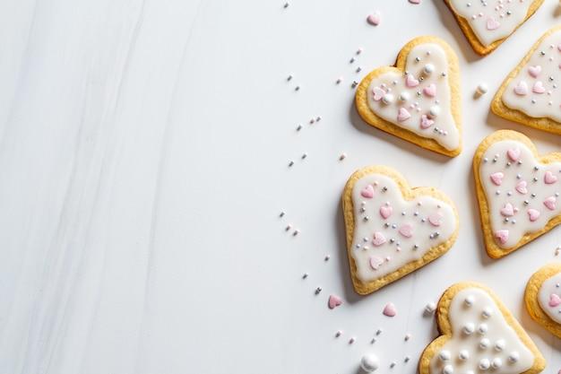 Koekjesharten met suikerglazuur en verfraaid voor valentijnsdag, witte achtergrond, exemplaarruimte.
