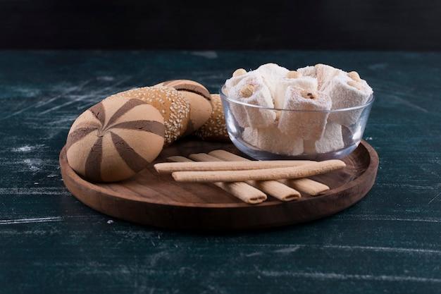 Koekjesplaat met broodjes, lokum in een glazen beker en wafelstokjes