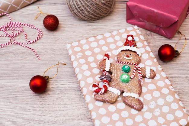 Koekjessneeuwman op gift dichtbij kerstmisballen