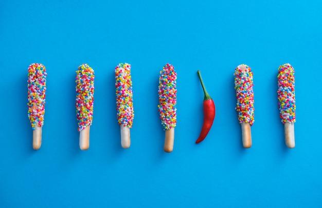 Koekjesstok met een laag bedekt met regenboog en spaanse pepers op blauwe achtergrond