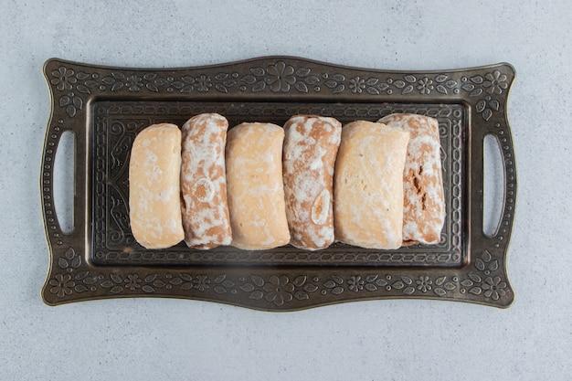 Koekjesverpakkingen op een sierlijke dienblad op marmeren achtergrond.