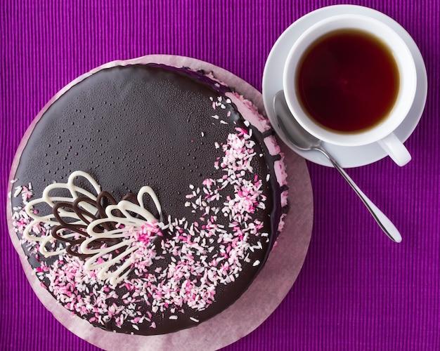 Koektaart met fruitsoufflé, versierd met chocolade en kopje thee. bovenaanzicht