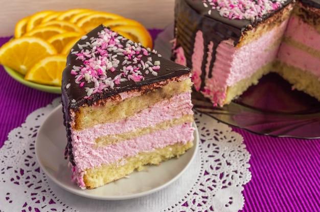 Koektaart met fruitsoufflé, versierd met chocolade en kopje thee. piece of cake is geïsoleerd.