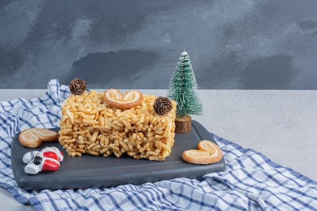 Koektaart met schilferige koekjes en kerstversieringen op een bord op marmeren oppervlak