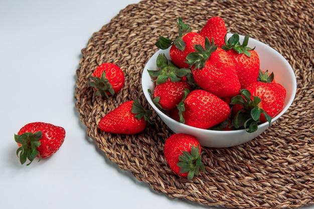 Koel aardbeien in een witte kom op een grijze gradiënt en ronde placematachtergrond. zijaanzicht.