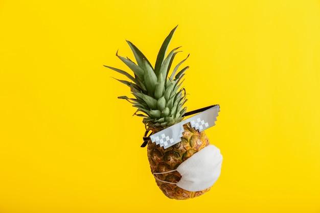 Koel gezicht op ananas in beschermende medische maskerzonnebril. zwevende tropische ananas fruit geïsoleerd op gele zomer achtergrond. minimalistisch concept van covid coronavirus in reisvakantie.