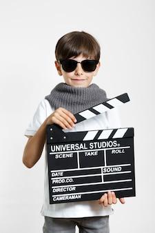 Koel jong kind met zonnebril en clapperboard