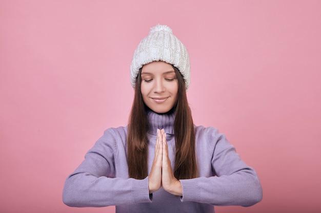 Koel kalm meisje in het koude seizoen dat zich kalm met gevouwen wapens bevindt alsof biddend