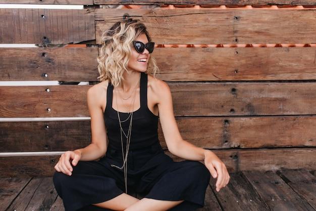 Koel meisje met golvend haar zittend met gevouwen benen. lachende gelooide vrouw in zonnebril doet yoga op houten muur.