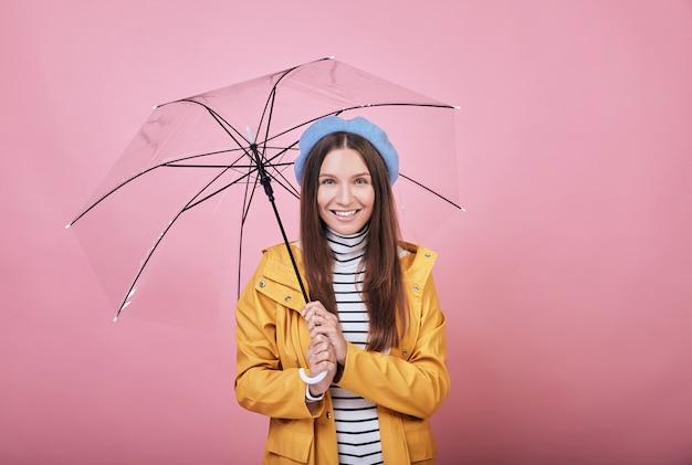 Koel mooi meisje in geel regenjasje met paraplu