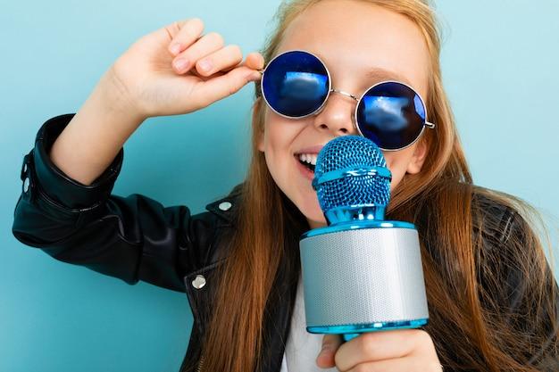 Koel opgewekt meisje dat een lied zingt in een microfoon op een blauwe achtergrond
