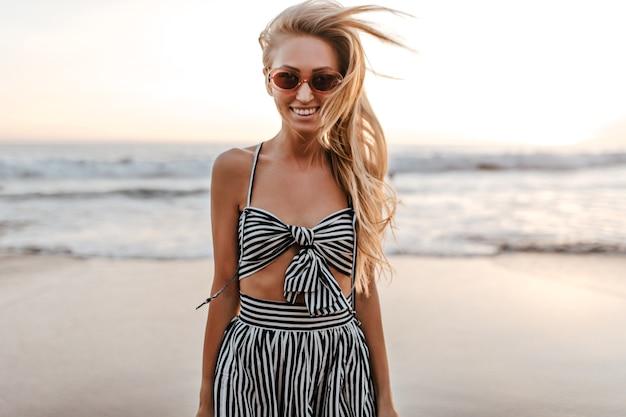 Koele actieve vrouw in gestreepte bijgesneden top en rok glimlacht oprecht in de buurt van zee