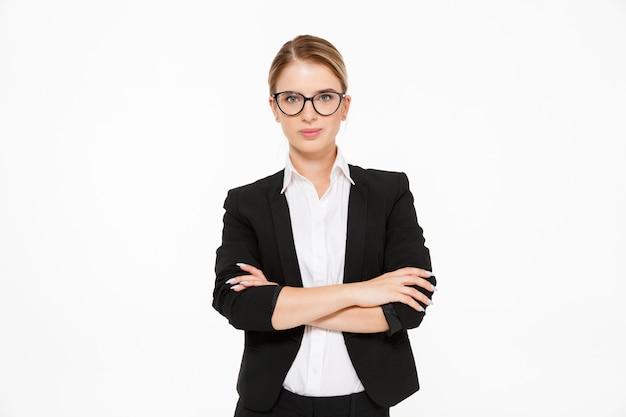 Koele blonde bedrijfsvrouw in oogglazen die met gekruiste wapens over wit stellen