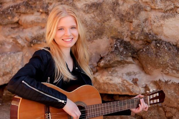 Koele blondemeisje het spelen gitaar openlucht