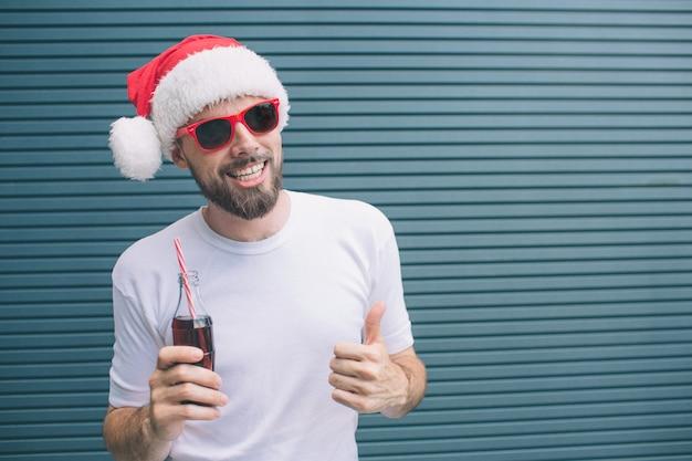 Koele en geweldige kerel staat en poseren op camera. hij houdt een fles cola in de hand en toont een grote duim op een andere. man draagt hoed en bril. geïsoleerd op gestreept