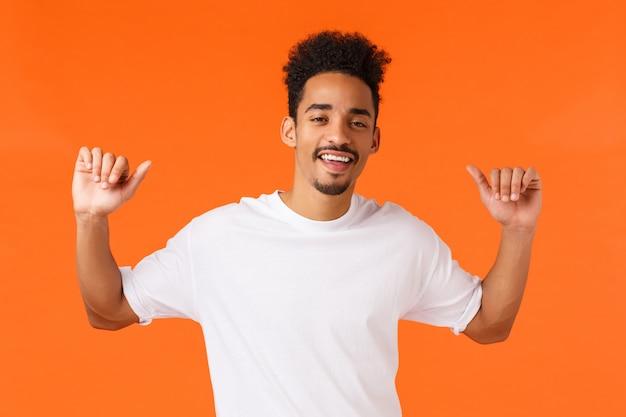 Koele en stijlvolle, opschepperige afro-amerikaanse man met tatoeages, snor, wijzende duimen naar zichzelf en grijns brutaal, assertief en zelfverzekerd, trotse eigen prestatie, oranje muur