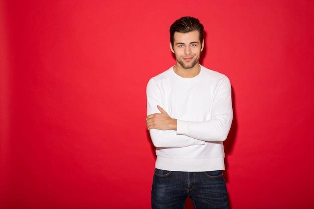 Koele glimlachende mens die in sweater met gekruiste wapens over rode muur kijken
