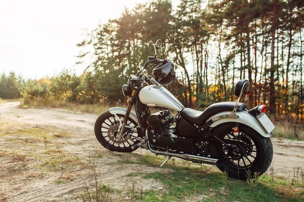 Koele grote fiets staat op een zanderige landweg tegen de achtergrond van een dennenbos en een prachtige zonsondergang