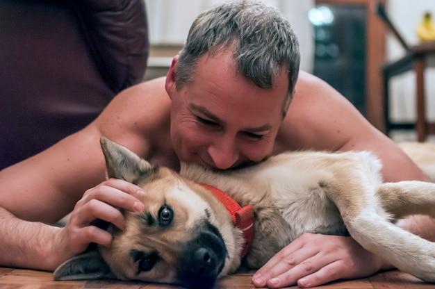 Koele hond en volwassen man met plezier thuis. glimlachende man en hond
