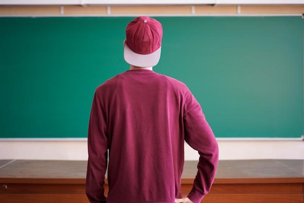 Koele jonge hipsterstudent in snapback glb en toevallig op universiteit met bord op achtergrond