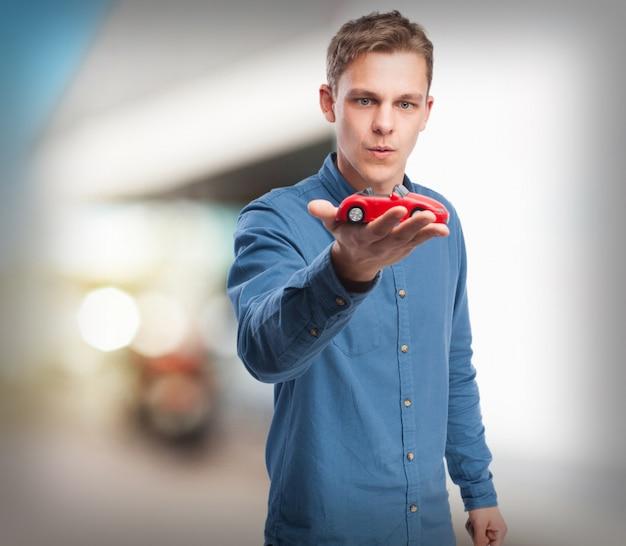 Koele jonge man met een rode auto