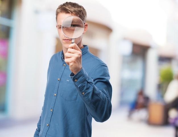 Koele jonge man met een vergrootglas