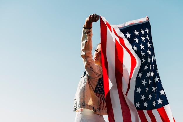 Koele jonge vrouw die amerikaanse vlag houdt die over schouder kijkt