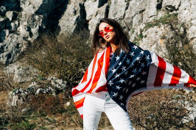 Koele jonge vrouw die in vlag wordt verpakt die zich in aard bevindt