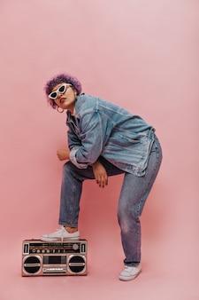 Koele jonge vrouw in oversized jeansjasje en in spijkerbroek die zich voordeed. stijlvolle vrouw in blauwe kleren en witte glazen
