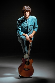 Koele kerel die zich met gitaar op dark bevindt