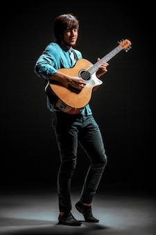 Koele kerel die zich met gitaar op donkere achtergrond bevindt