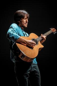 Koele kerel die zich met gitaar op donkere muur bevindt