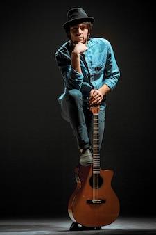 Koele kerel die zich met gitaar op donkere ruimte bevindt