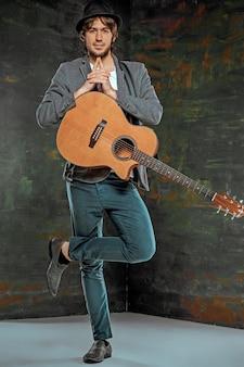 Koele kerel die zich met gitaar op grijs bevindt