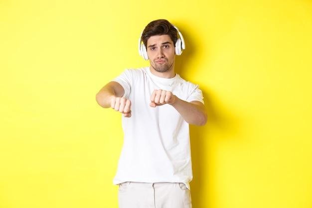 Koele kerel luisteren muziek in hoofdtelefoons en dansen, staande in witte kleren tegen gele studio achtergrond.