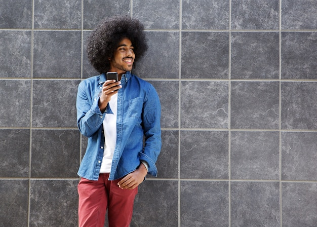 Koele kerel met afro die cellphone gebruikt
