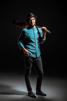 Koele kerel met hoed die zich met gitaar op donkere studioachtergrond bevindt