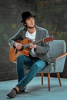Koele kerel met hoed gitaarspelen op grijze achtergrond