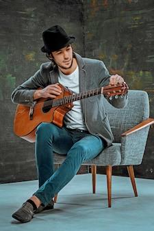 Koele kerel met hoed gitaarspelen op grijze studioachtergrond